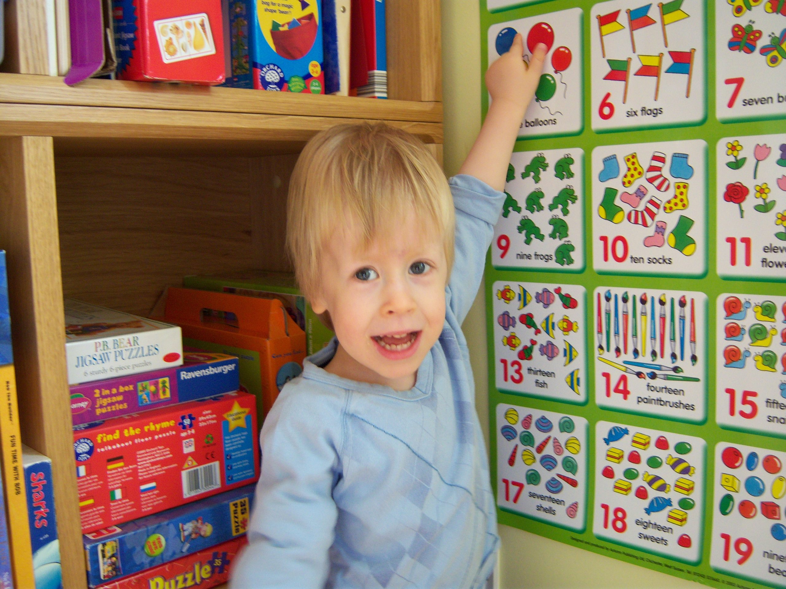 young child pointing at maths number wall