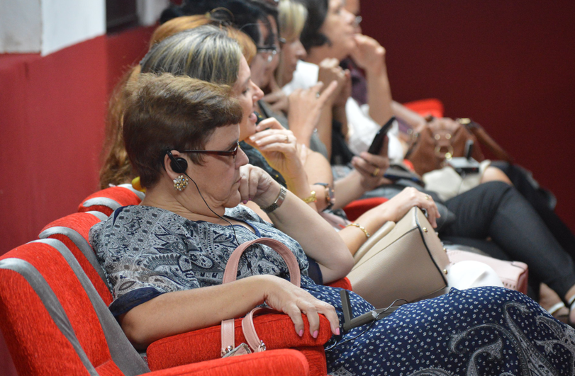 lady with listening device on row of red seats