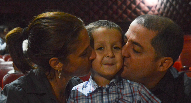 parents kissing a boy on either side of his face
