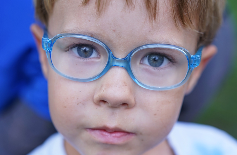 young boy with blonde hair and blue glasses